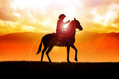 Lonesome Cowboy. Silhouette illustration of a cowboy riding a horse during sunset Stock Photo