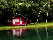 Lonesome red cabin at shallow lake with lights on