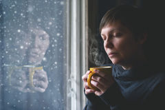 Lonesome Woman Drinking Coffee in Dark Room. Lonelsome woman drinking cup of coffee by the window of her living room while the snow is falling outside. Selective royalty free stock images