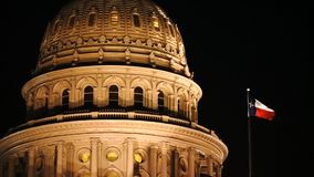 Lonestar State Flag Waves Austin Capital Building Night. A tight shot of the Texas flag waving next to the capital dome in Austin stock video