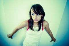 Loney Girl. A young woman backs herself to the wall, seemingly scared or lonely stock image