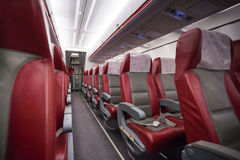 Long aisle with rows of sits in airlane. Empty saloon of commercial airplane with rows of red generic seats in the aisle Royalty Free Stock Image