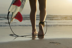 Long angle of surfer walking along beach with ankle leash and board fins. At sunrise Stock Image