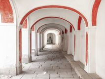 Long arcade corridior with white and red facade and cobbled floor.  Royalty Free Stock Image