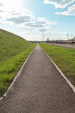 Long asphalt path next to green hill on sunny spring day Stock Photography