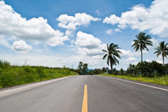 Long asphalt road with the blue sky. Stock Photos