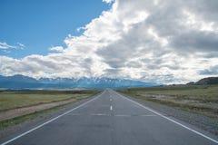 Long asphalt road. Mountains in the horizon. Stock Photo