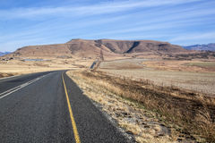 Long Asphalt Road Stretching through Dry Winter Landscape Royalty Free Stock Photo
