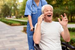 Happy old man sitting in a wheelchair and talking to someone on the phone Royalty Free Stock Photo