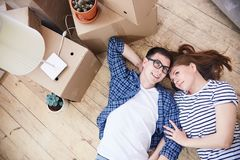 Long-Awaited Cohabitation of Young Couple. Lovely young couple lying on wooden floor of their new apartment and sharing ideas concerning interior design of royalty free stock image