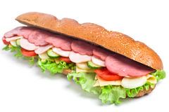 Long baguette sandwich. Long whole wheat baguette sandwich with lettuce, tomatoes, cucumbers, ham, turkey breast and cheese Stock Image