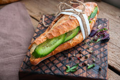 Long baguette sandwich with beef steak slices cucumber and spice. S on a wooden board. Rustic style. Close up and copy space Stock Images