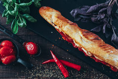 Long baguette sandwich with lettuce, vegetables, salami, chili and cheese on black background.  Royalty Free Stock Image