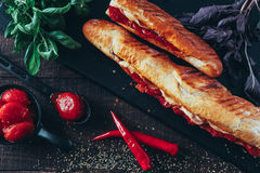 Long baguette sandwich with lettuce, vegetables, salami, chili and cheese on black background.  Stock Photo