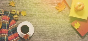 Long banner of autumn red, green and yellow leaves, apples with cup of coffee or tea with books on vintage background. Stock Image