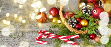 Long banner Christmas Basket with Gifts and Shining lights. Red balls, Pine cones, lollipop on Wooden Table Royalty Free Stock Photography