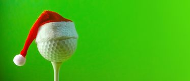 A long banner with copy space on the subject of golf at Christmas and in the new year. A red Santa Claus hat is worn on a golf