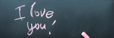 Long banner with Message I Love You Lettering. Writteng pink chalk on black chalkboard Valentine`s Day royalty free stock images