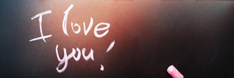 Long banner with Message I Love You Lettering. Writteng pink chalk on black chalkboard Valentine`s Day Dark effect royalty free stock photography