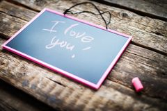 Long banner with Message I Love You Lettering. Message I Love You Handwritting lettering pink chalk on black chalkboard desk Valentine`s Day Wooden Background royalty free stock image
