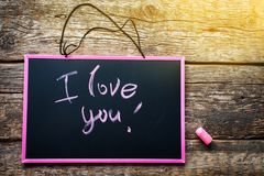 Long banner with Message I Love You Lettering. Message I Love You Handwritting lettering pink chalk on black chalkboard desk Valentine`s Day Wooden Background royalty free stock images