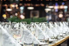 A long banquet table with wineglasses and serviettes. View from the left side Royalty Free Stock Image