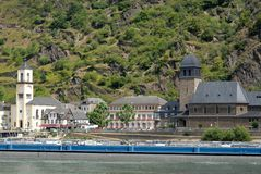 Long barge and a small village with two churches on the banks of the Rhine River in Germany Royalty Free Stock Photos