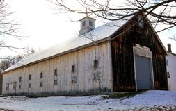 Long Barn on a Grey New England morning. White cupola old wooden barb grey sides brown front snow depressing sky big barn door, middlesex county, Massachusetts stock photography