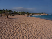 Long Beach in Cabo Mexico. Yellow sandy beach with  palapa beach umbrellas. Blue sky with some clouds, late afternoon, long shadows. Cabo San Lucas Baja Mexico Stock Photo