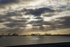 Long Beach in California with sunrays and crane and ship silhouettes royalty free stock photography