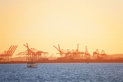 Long Beach shipping port with cranes at sunset. Long Beach shipping port with loading cranes` silhouettes at sunset, California, USA Stock Images
