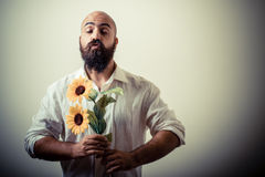 Long beard and mustache man giving flowers. On gray background Royalty Free Stock Images