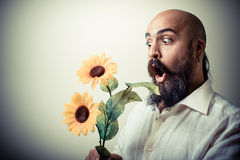 Long beard and mustache man giving flowers Stock Photo