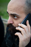 Long bearded man on the phone Stock Images