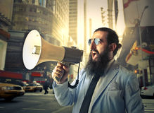 Long-bearded man. Shouting into a megaphone Stock Images