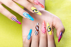 Long beautiful manicure in pop-art style on female fingers. Nails design. Close-up.  royalty free stock photo