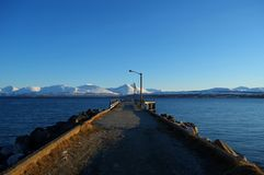 Long beautiful pier with snowy mountain and blue fjord Royalty Free Stock Image