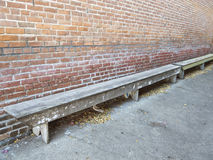 Long benches along a brick wall Royalty Free Stock Photo