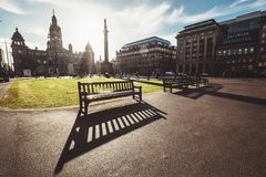 Long benches shadows on the George Square - the principal civic. Square in the city of Glasgow, Scotland royalty free stock photos