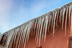Long big icicles on the roof of an old house against a blue sky Royalty Free Stock Photos