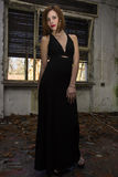 Long Black Dress. Beautiful young model posing in a long black dress, in abandoned place Royalty Free Stock Photo