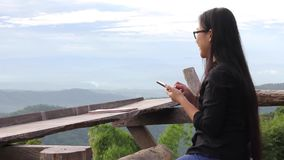 Long black hair Asian women wearing glasses play mobile or smartphone in background of mountain forest top view. Smiling happy girl in nature with technology
