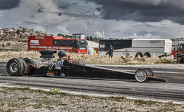 Long black racing car with driver Stock Photos