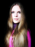 Long blond hair. Portrait of a woman in pink with long blond hair on black background royalty free stock photo