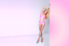 Long blond hair young sexy woman standing on the ass in a pink sexy dress made of plastic Royalty Free Stock Image