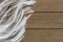 Long blonde feminine wig on a wooden background royalty free stock photography