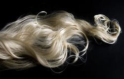Long blond hair on black background stock image