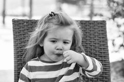 Cute baby boy eating tasty ice cream in outdoor cafe. Long blonde stylish hair, adorable baby boy, small, little child in blue, striped clothes eating tasty ice stock image