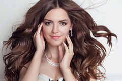 Long blowing hair. Beautiful brunette girl model with makeup, fa. Shion jewelry, wavy hairstyle Royalty Free Stock Photography