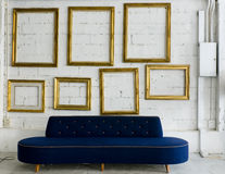 Long blue fabric sofa and gold picture frame. On white wall Royalty Free Stock Photography